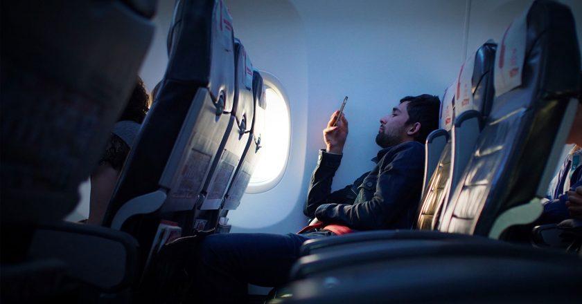 Mann im Flugzeug betrachtet programmatische Werbung